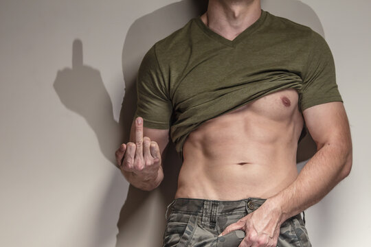 a man, a soldier holding his dick and shows middle finger, fuck off attitude
