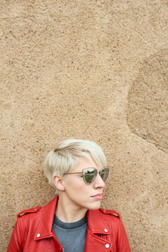 Headshot of stylish blonde in red leather jacket and sunglasses looking away