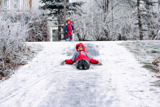 Boy slides down an icy path in winter while his brother watches, laughing