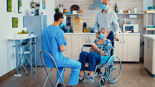 Handicapped senior woman in wheelchair wearing face mask discussing with doctor about treatment. Social worker offering pills to handicapped elderly woman. Geriatrician helping prevent covid-19 spread