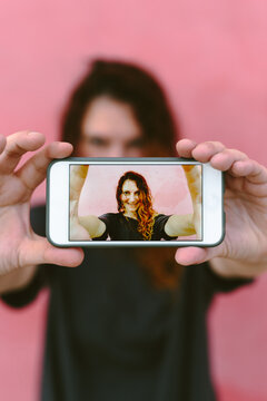 Woman taking a selfie with cell phone