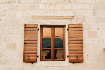 The wall of the house is white brick with new brown wooden shutters and a tinted window.