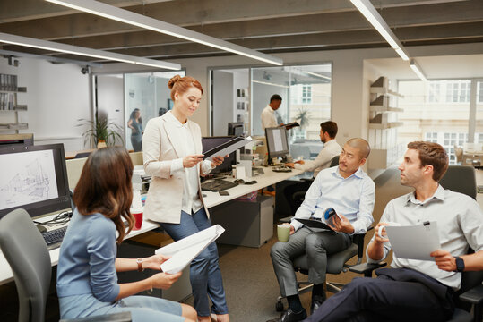 Business team looking at redhead leaning against desk
