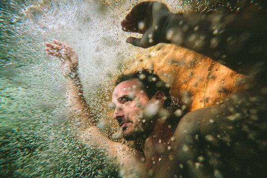 Portrait of a peaceful calm man floating underwater surrounded by bubbles