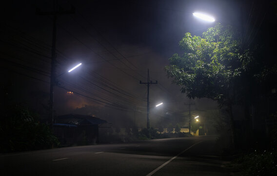 Empty road underneath street light at night with UFO on back
