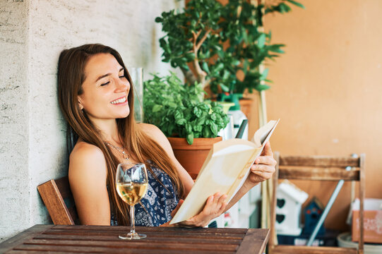 Young happy woman relaxing on the balcony, reading book, leaning on the wall, drinking glass of wine