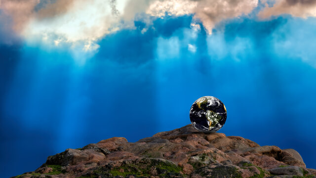 The planet earth on a rock against a dramatic blue sky with shards of sunlight filtering through the clouds