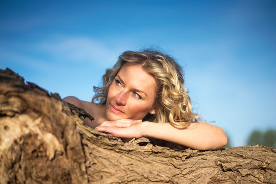 verträumte  junge Frau  am Baum