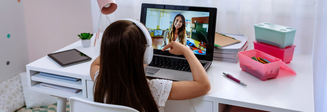 Unrecognizable girl at home receiving online class from her teacher via laptop