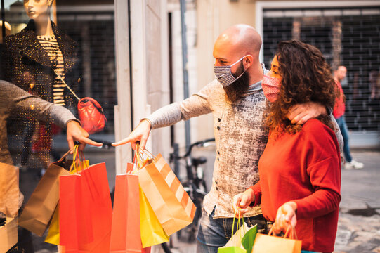 Beautiful young couple enjoying in shopping, having fun together, with the face mask