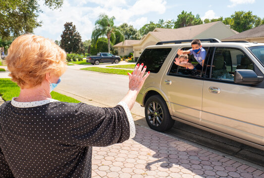 Grandchildren wearing face mask visit their grandmother at her home, driving by and waving  to her from a safe social distance during coronavirus pandemic.