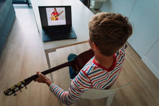 young boy having guitar lesson online at home