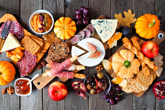 Fall theme charcuterie table scene against a dark wood background. Different cheese and meat appetizers. Top down view.
