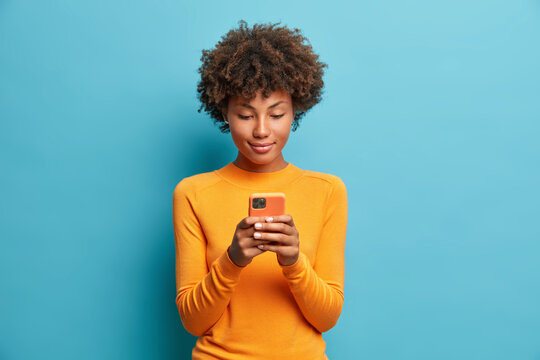 Calm serious dark skinned young woman plays games on phone or sends text messages connected to high speed internet uses modern technologies dressed in casual jumper poses against blue background.