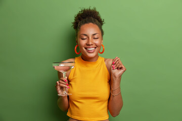 Happy pleased dark skinned woman closes eyes and smiles toothily raises clenched fist and drinks...