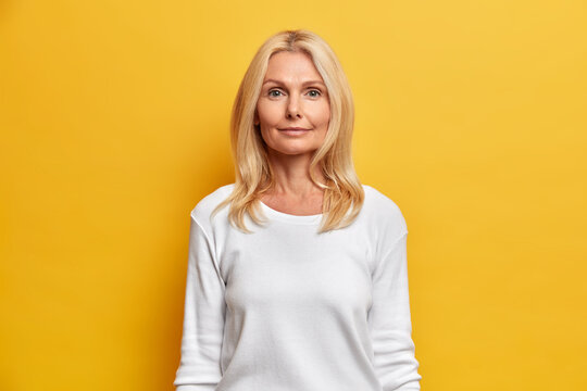 Portrait of good looking middle aged woman with wrinkled face natural beauty blonde hair looks directly at camera has calm expression dressed in white casual jumper isolated on yellow studio wall