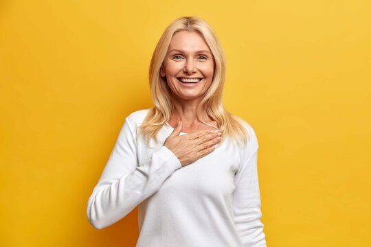 Happy grateful blonde woman in her fifties holds hand on chest and smiles broadly swears be loyal thanks for honesty smiles gladfully dressed in casual white jumper isolated on yellow background