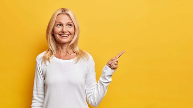 Happy senior woman shows copy space against yellow background smiles pleasantly and has dreamy expression demonstrates vacant advertising spot wears white jumper recommends good offer or discount
