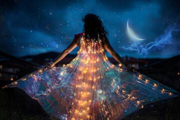 Obraz Belly dancer with wings of light under a starry sky - fototapety do salonu