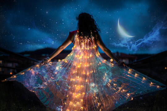 Belly dancer with wings of light under a starry sky