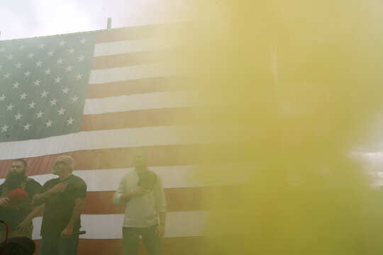 Yellow smoke is seen as people sing the national anthem during a rally of the far right group Proud Boys, in Portland