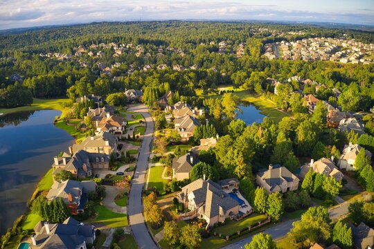 Beautiful aerial view of a sub division with golf course and a beautiful lake  in suburbs of Atlanta during golden hour.