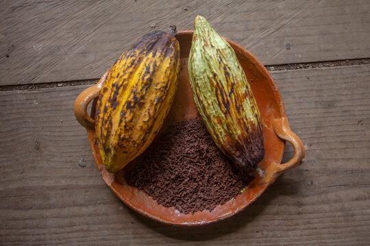 Vainas de cacao molido sobre bandeja de barro sobre mesa de madera chocolate