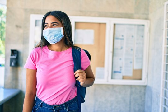 Young latin student girl wearing medical mask at university campus