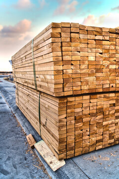 Vertical shot of pallet of 2x4 studs for house framing - lumber sitting on the sidewalk of a residential construction site