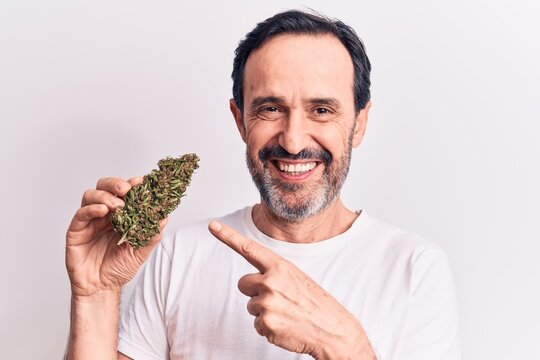 Middle age handsome man holding cannabis weed standing over isolated white background smiling happy pointing with hand and finger