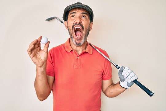 Middle age hispanic man holding golf club and ball angry and mad screaming frustrated and furious, shouting with anger looking up.