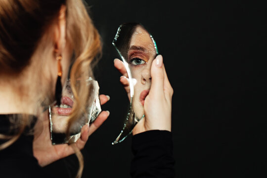 Serious woman looking at broken self-image mirror on black background