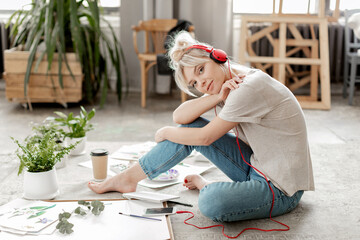 Creative beautiful young woman artist wearing headphones connected to smartphone, casual clothes...