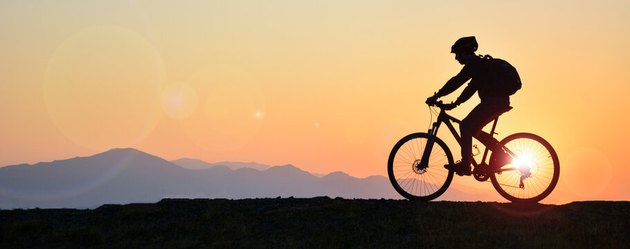 silhouette of a person riding a bike
