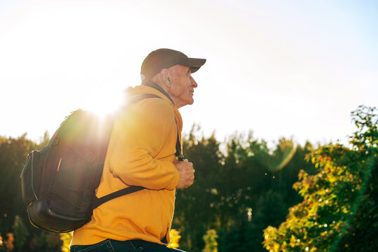 senior active tourist man with black backpack make fitness by hiking exercise in mountain
