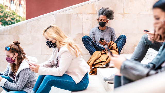 Urban millennial people using smart phones with face mask on Covid second wave - Serious guy watching news on mobile smartphone - College students sitting at university break - Bright contrast filter