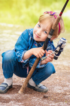Cute child is sitting and holding fishing rod in his hands.