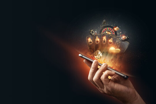 Creative background, online casino, in a man's hand a smartphone with playing cards, roulette and chips, black-gold background. Internet gambling concept. Copy space