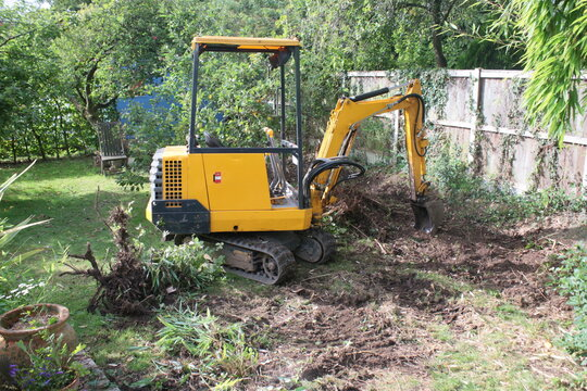 Yellow digger heavy motor machinery with digging arm moving earth, re-landscaping an organic garden lawn orchard area moving the soil to create level ground in outdoor growing space with trees & fence