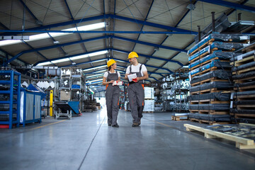 Fototapeta Factory workers in work wear and yellow helmets walking through industrial production hall and discussing about delivery deadline. obraz