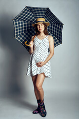 Pregnant woman in country style summer dress and straw hat standing under umbrella