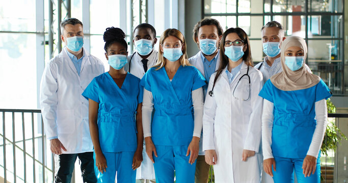Mixed-races busy team of male and female doctors posing to camera and crossing hands in hospital. International group of medics in medical masks. Protected multi ethnic physicians and nurses in clinic