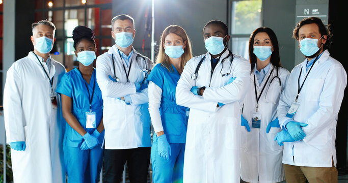 Multi ethnic women and men, doctors. International medics in medical masks. Protected healthcare workers. Mixed-races physicians and nurses looking at camera. Clinic team. Docs at work in hospital.
