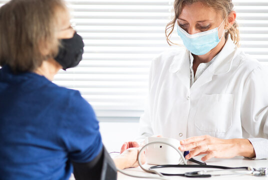 female doctor consulting a patient wearing medical mask