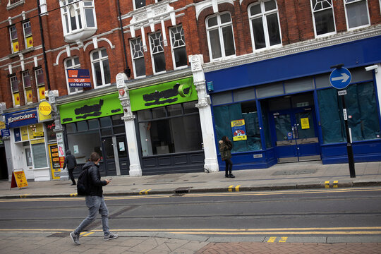 Pedestrians walk past closed retail stores in Croydon, south London