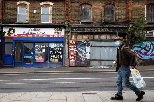 Pedestrian walks past closed retail stores in Croydon, south London,