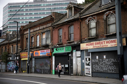 Pedestrians walk past shuttered and bordered up retails stores in Croydon, south London