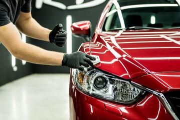 Obraz Car service worker applying nano coating on a car detail. - fototapety do salonu