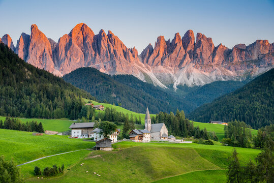 View of Val di Funes or Villnöß during sunset with Santa Magdalena church and Enrosadira or alpenglow effect on the Odle/Geisler massif, Val Gardena, Dolomites, South Tyrol, Italy