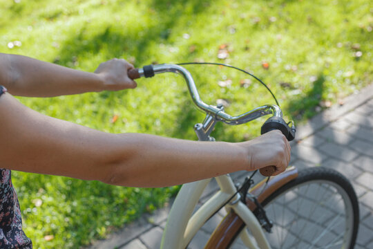 The girl holds the wheel of a beige bike in the park among green trees and lawn